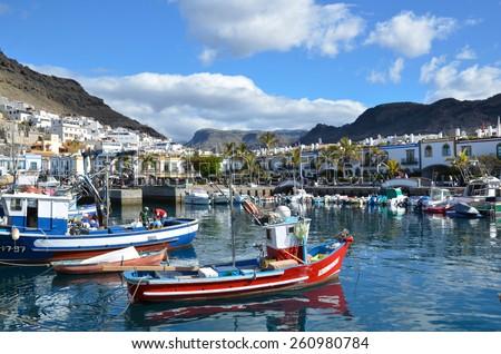 PUERTO DE MOGAN, SPAIN- FEBRUARY 13; Colorful canarian fishing boats at the harbor in Puerto de Mogan,.  Popular travel location and harbor. Photo taken on February 13,2015 in Mogan, Spain. - stock photo