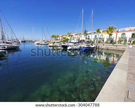 PUERTO DE MOGAN, SPAIN- JULY 23; View at yachts in the marina in Puerto de Mogan, Gran Canaria, Spain. A popular harbor for sailors. Photo taken on July 23,2014 in Mogan, Spain. - stock photo