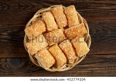 Puff biscuits with cheese in wicker plate on wooden background, top view