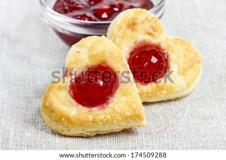 Puff pastry cookies in heart shape filled with cherries - stock photo