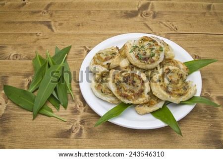 Puff pastry pinwheels filled with ham, cheese and chopped wild garlic - stock photo