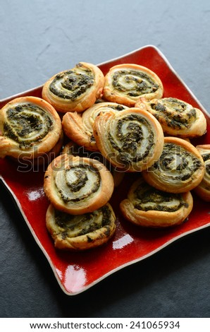 Puff pastry rolls with spinach and greek cheese filling on a stone plate - stock photo