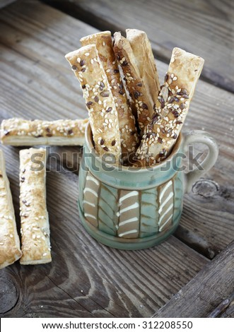 Puff pastry sticks with sesame seeds in a ceramic bowl - stock photo