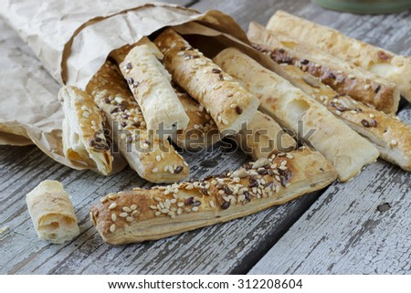 Puff pastry sticks with sesame seeds in a paper bag - stock photo