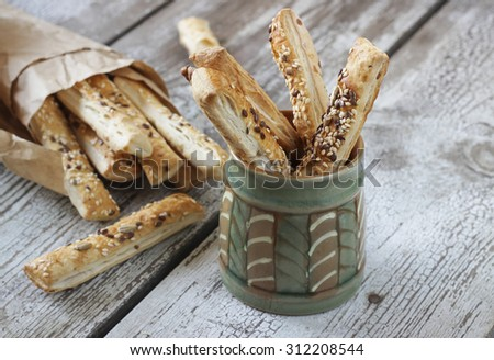 Puff pastry sticks with sesame seeds in a paper bag and ceramic bowl - stock photo