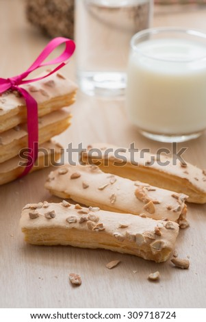 Puff pastry topping with sugar and nut, with milk glass on wood table.