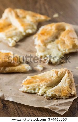 Puff pastry with cheese on baking paper. Homemade baking on a wooden background