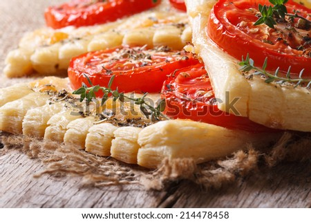 Puff pie with tomato, cheese and herbs on the table macro. horizontal  - stock photo