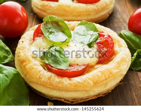 Puff-pizzas with mozzarella cheese, cherry tomatoes and baby basil. Shallow dof.