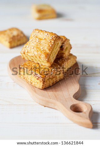 Puff square pastry with sesame on wooden table - stock photo
