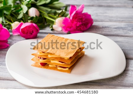 Puff with custard on plate. Bright pink flowers. Raspberry millefeuille served at restaurant. Sweet dish for a gourmet. - stock photo