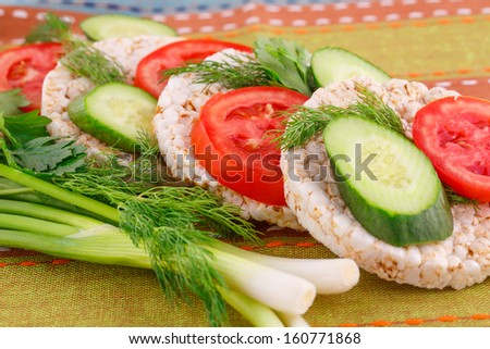 Puffed rice crackers sandwiches with vegetables on tablecloth. - stock photo