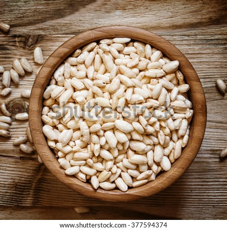 Puffed sweet rice in a round bowl on the old wooden background, top view - stock photo