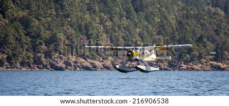 PUGET SOUND, WASHINGTON - AUGUST 4, 2014: A commercial seaplane lands at Orcas Island. - stock photo