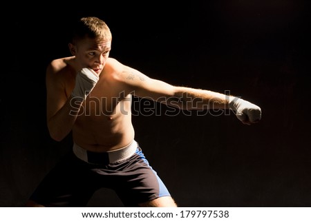 Pugnacious young boxer throwing a punch during a fight with a look of determination against a dark shadowy background - stock photo