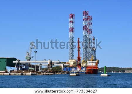 PULA, CROATIA - AUGUST 15, 2017: Cargo harbor of Pula town with cranes, warehouses and big red cargo ship with blue sky background.