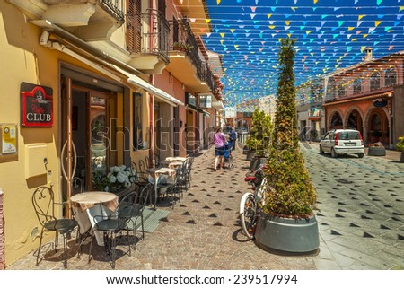 PULA, SARDINIA, ITALY - MAY 16 2014 : Streets of Pula city decorated with flags with tourists and locals walking - stock photo