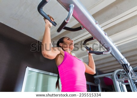 Pull ups Pull-up exercise workout girl at gym exercises - stock photo