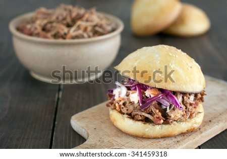 Pulled pork burger with red cabbage salad and bbq sauce in a homemade bun - stock photo