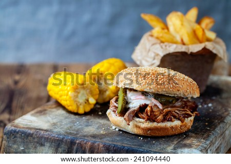 Pulled pork burger with sweet corn and chips - stock photo