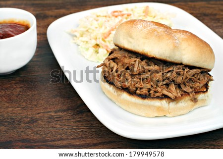 Pulled pork sandwich on a potato bun with a side of cole slaw and barbecue sauce for dipping. - stock photo