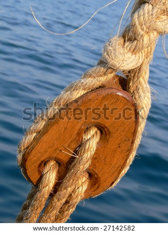 Pulley block on an old wooden sail boat with ropes (rigging element) - stock photo