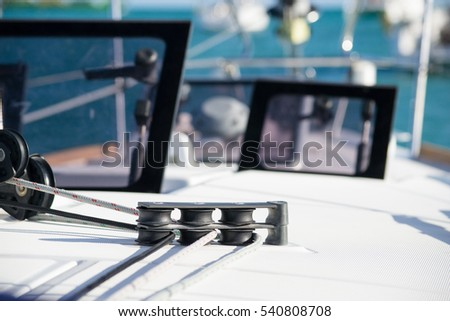 Pulleys on the deck of a yacht with sheets/ropes