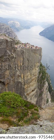 Pulpit Rock with many tourists at Lysefjorden in Norway. A well known tourist attraction towering 604 meters - stock photo