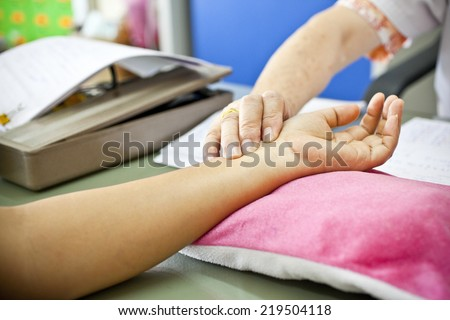 Pulse being taking on a middle aged woman's wrist - stock photo