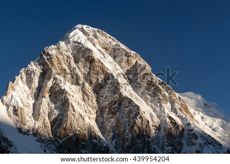 Pumori mountain peak on the famous Everest Base Camp trek in Himalayas, Nepal. Snowy mountain summit in the early morning with clear sky. Beautiful mountain peak landscape in Himalayas.
