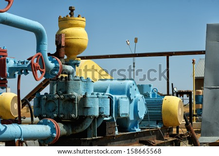 Pump is pumping oil is colored blue, close-up. - stock photo