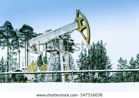 Pump jack and wellhead in the oilfield situated in the beautiful winter forest. Environmental pollution. Oil and gas concept.