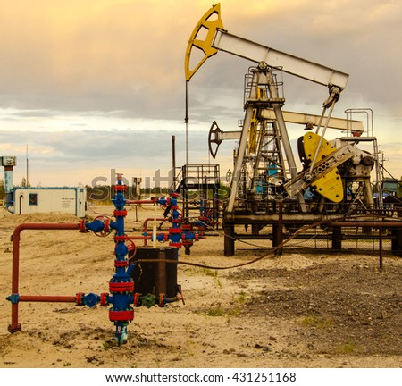 Pump jack and wellhead in the oilfield. Sunset sky background. Oil and gas concept. Toned. - stock photo