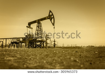 Pump jack and wellheads. Extraction of oil. Toned.