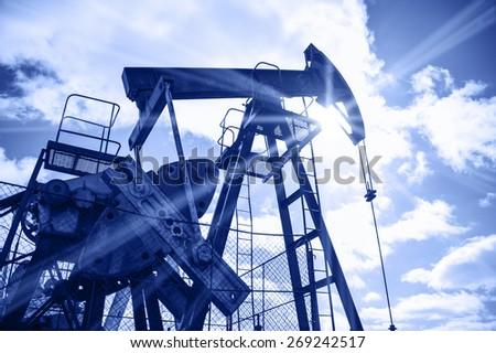 Pump jack on a sky and sun background. Extraction of oil. Toned blue.