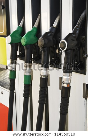 Pump nozzles at the gas station (selective focus) - stock photo