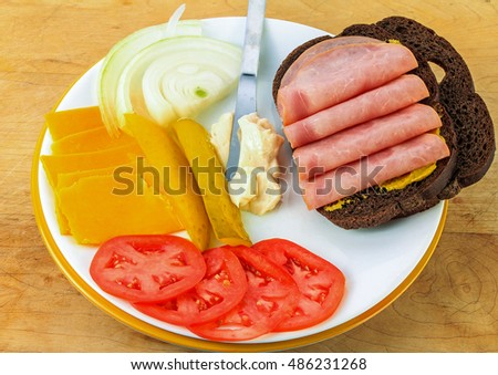 Pumpernickel on white plate with ingredients for ham and cheese sandwich.