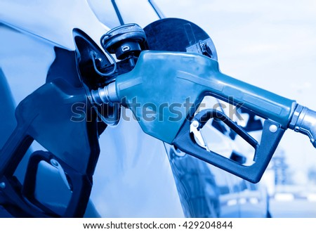 Pumping gas at gas pump - stock photo