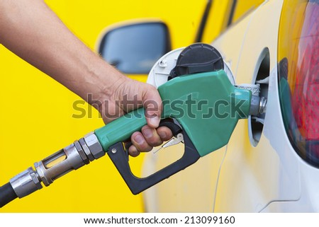 Pumping gas at gas pump. Closeup of man pumping gasoline fuel in car at gas station - stock photo