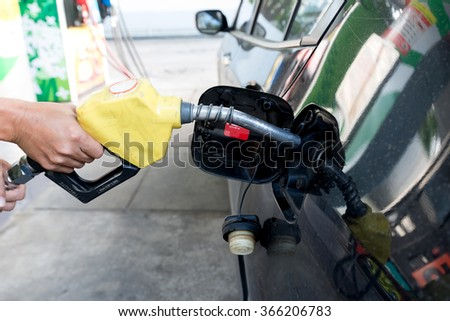 Pumping gas at gas pump. Closeup of man pumping gasoline fuel in car at gas station
