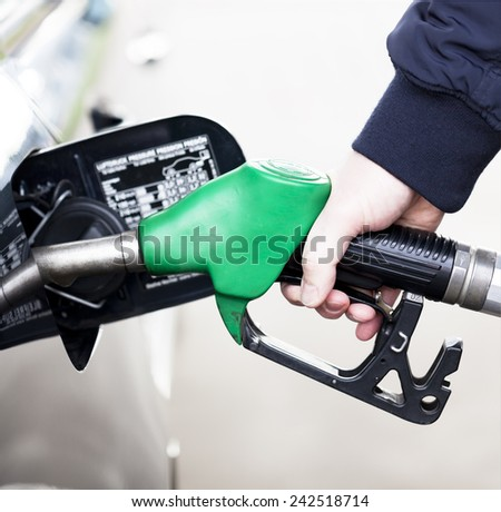 Pumping gas at gas pump. Closeup of man pumping gasoline fuel in car at petrol station  - stock photo