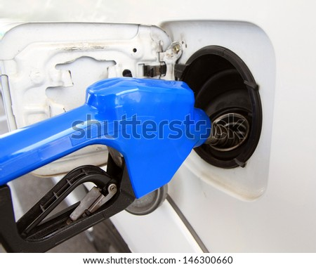 Pumping gas at gas station - stock photo