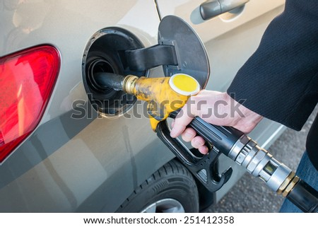 Pumping gas. Close up of man pumping fuel in car at gas station.