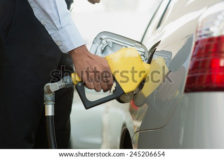 Pumping gas. Close up of man pumping gasoline fuel in car at gas station. - stock photo