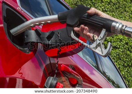 Pumping Gas - Filling a cars fuel tank with diesel or petrol  - stock photo