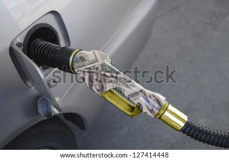 Pumping gas from a golden - Cash nozzle - stock photo