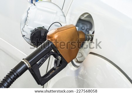pumping gasoline fuel in car at gas station - stock photo