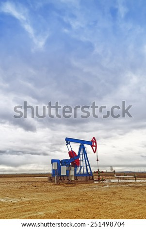 Pumpjack Oil Pump operating on natural gas in the field pumping from the oil well. - stock photo