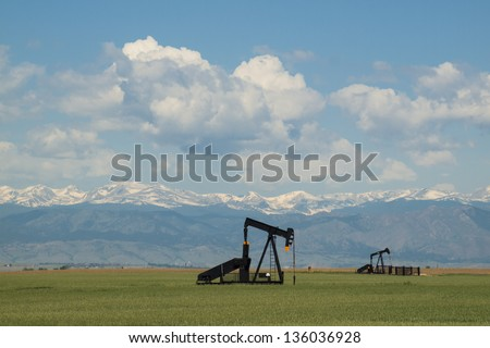 Pumpjack on agricultural field in Colorado. - stock photo