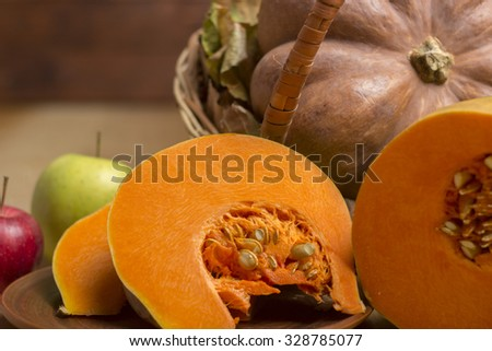 Pumpkin and apple autumn leaves on a wooden table